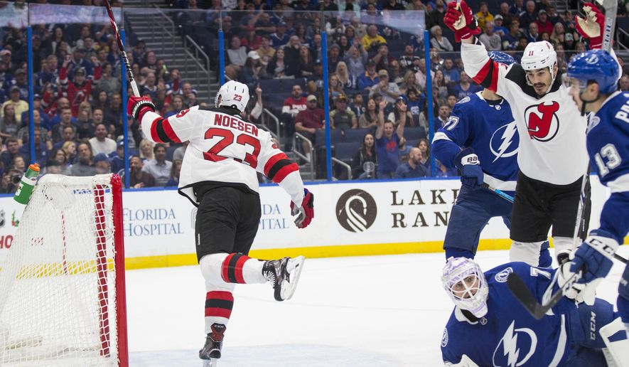 New Jersey Devils right wing Stefan Noesen (23) and center Brian Boyle celebrate a goal on Tampa Bay Lightning goaltender Louis Domingue (70) laying on the ice during the first period of an NHL hockey game, Sunday, Nov. 25, 2018, in Tampa, Fla. (AP Photo/Willie J. Allen Jr.)