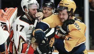 Anaheim Ducks center Ryan Kesler (17) and Nashville Predators left wing Filip Forsberg (9), of Sweden, fight as linesman Jonny Murray, center, tries to pull them apart during the second period of an NHL hockey game Sunday, Nov. 25, 2018, in Nashville, Tenn. (AP Photo/Mark Humphrey)