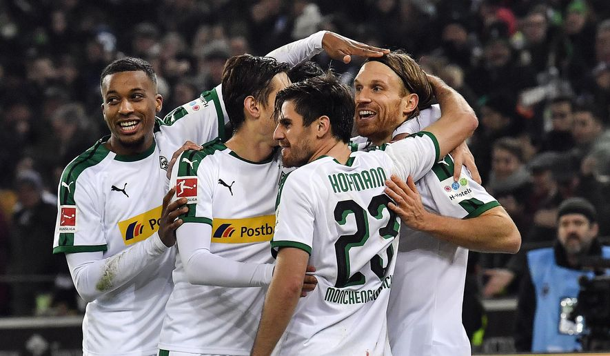 Moenchengladbach's Michael Lang, right, is celebrated after scoring his side's second goal during the German Bundesliga soccer match between Borussia Moenchengladbach and Hannover 96 at the Borussia Park in Moenchengladbach, Germany, Sunday, Nov. 25, 2018. (AP Photo/Martin Meissner)