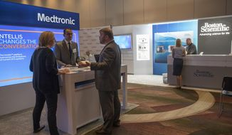 In this Saturday, Aug. 25, 2018 photo, sales representatives for Medtronic and Boston Scientific work their booths at the NYC Neuromodulation Conference in New York. For years, medical device companies and doctors have touted spinal cord stimulators as a panacea for millions of patients suffering from a wide range of intractable pain disorders. But the devices, surgically placed inside the back, that use electrical currents to block pain signals before they reach the brain _ are more dangerous than many patients understand, according to an Associated Press investigation. (AP Photo/Mary Altaffer)