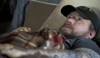 In this Friday, Nov. 16, 2018 photo, Jim Taft watches The History Channel from the confines of his bed at his home in West Columbia, S.C. Taft has experienced debilitating health issues after a neurosurgeon implanted Boston Scientific's Precision spinal cord stimulator in his back in 2014. (AP Photo/Sean Rayford)