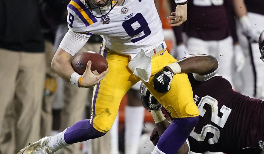 LSU quarterback Joe Burrow (9) is tackled by Texas A&M defensive lineman Justin Madubuike (52) during the first half of an NCAA college football game Saturday, Nov. 24, 2018, in College Station, Texas. (AP Photo/David J. Phillip)