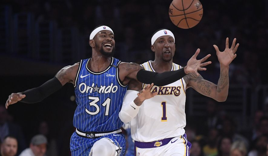 Orlando Magic guard Terrence Ross, left, and Los Angeles Lakers guard Kentavious Caldwell-Pope reach for a loose ball during the first half of an NBA basketball game Sunday, Nov. 25, 2018, in Los Angeles. (AP Photo/Mark J. Terrill)