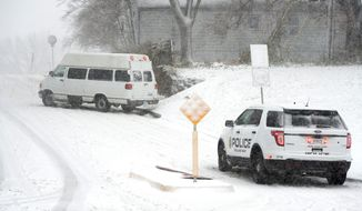 Police from Roeland Park, Kan., watched as the driver of a van tried to a navigate a slick street Sunday, Nov. 25, 2018, that hit the Kansas City area. A winter storm blanketed much of the central Midwest with snow on Sunday at the end of the Thanksgiving weekend, bringing blizzard-like conditions that grounded hundreds of flights and forced the closure of major highways on one of the busiest travel days of the year. (Tammy Ljungblad/The Kansas City Star via AP)