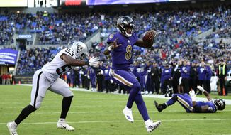 Baltimore Ravens quarterback Lamar Jackson (8) scores a touchdown in front of Oakland Raiders linebacker Jason Cabinda in the second half of an NFL football game, Sunday, Nov. 25, 2018, in Baltimore. (AP Photo/Nick Wass)