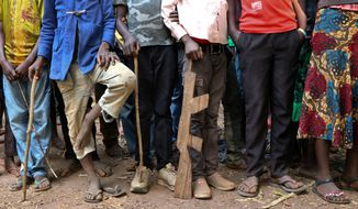 """FILE - In this Wednesday, Feb. 7, 2018 file photo, former child soldiers stand in line waiting to be registered with UNICEF to receive a release package, in Yambio, South Sudan. In an interview with The Associated Press in civil war-torn South Sudan, Romeo Dallaire, the former commander of the failed U.N. peacekeeping mission during the Rwandan genocide, says the current approach to combatting child soldier recruitment is not """"sufficient"""". (AP Photo/Sam Mednick, File)"""