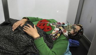 In this photo released by the Syrian official news agency SANA, shows a woman receiving oxygen through respirators following a suspected chemical attack on her town of al-Khalidiya, in Aleppo, Syria, Saturday, Nov. 24, 2018. Some 50 civilians were being treated following a suspected poison gas attack by Syrian rebel groups on the government-held Aleppo city in the country's north, according to Syrian state media. (SANA via AP)