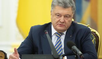 Ukrainian President Petro Poroshenko leads the National Security and Defence Council meeting in Kiev, Ukraine, Sunday, Nov. 25, 2018. Russia's coast guard opened fire on and seized three of Ukraine's vessels Sunday, wounding two crew members, after a tense standoff in the Black Sea near the Crimean Peninsula, the Ukrainian navy said. (Mykhailo Markiv, Presidential Press Service via AP, Pool)