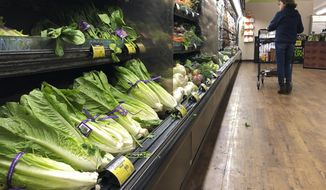 Romaine lettuce still sits on the shelves as a shopper walks through the produce area of an Albertsons market Tuesday, Nov. 20, 2018, in Simi Valley, Calif. Health officials in the U.S. and Canada told people Tuesday to stop eating romaine lettuce because of a new E. coli outbreak. (AP Photo/Mark J. Terrill)