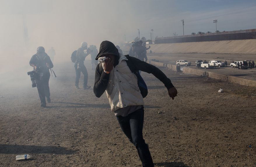 A migrant runs from tear gas launched by U.S. agents, amid members of the press covering the Mexico-U.S. border, after a group of migrants got past Mexican police at the Chaparral crossing in Tijuana, Mexico, Sunday, Nov. 25, 2018. The mayor of Tijuana has declared a humanitarian crisis in his border city and says that he has asked the United Nations for aid to deal with the approximately 5,000 Central American migrants who have arrived in the city.  (AP Photo/Rodrigo Abd)