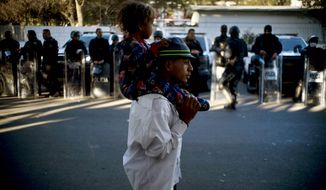 A migrant carries a child past Mexican police who stand guard outside the Benito Juarez Sports Center which is serving as a shelter for migrants in Tijuana, Mexico, Monday, Nov. 26, 2018. The mayor of Tijuana has declared a humanitarian crisis in his border city and says that he has asked the United Nations for aid to deal with thousands of Central American migrants who have arrived. (AP Photo/Ramon Espinosa)