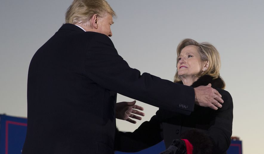 President Donald Trump embraces Sen. Cindy Hyde-Smith, R-Miss., during a rally at Tupelo Regional Airport, Monday, Nov. 26, 2018, in Tupelo, Miss. (AP Photo/Alex Brandon)
