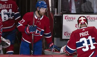 FILE - In this Nov. 8, 2018, file photo, Montreal Canadiens' Karl Alzner (27)and goaltender Carey Price leaves the ice after allowing an overtime goal loss to the Buffalo Sabres in an NHL hockey game in Montreal. The Canadiens have placed defenseman Karl Alzner on waivers. (Paul Chiasson/The Canadian Press via AP, File) **FILE**