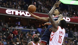Washington Wizards guard Bradley Beal, center, goes to the basket against Houston Rockets center Clint Capela (15) and guard James Harden, lower left, during the second half of an NBA basketball game, Monday, Nov. 26, 2018, in Washington. (AP Photo/Nick Wass) ** FILE **