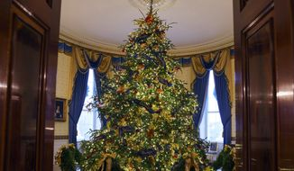 "The official White House Christmas tree is seen in the Blue Room during the 2018 Christmas Press Preview at the White House in Washington, Monday, Nov. 26, 2018. The tree measures 18 feet tall and is dressed in more than 500 feet of blue velvet ribbon embroidered in gold with each State and territory. Christmas has arrived at the White House. First lady Melania Trump unveiled the 2018 White House holiday decor on Monday. She designed the decor, which features a theme of ""American Treasures."" (AP Photo/Carolyn Kaster)"