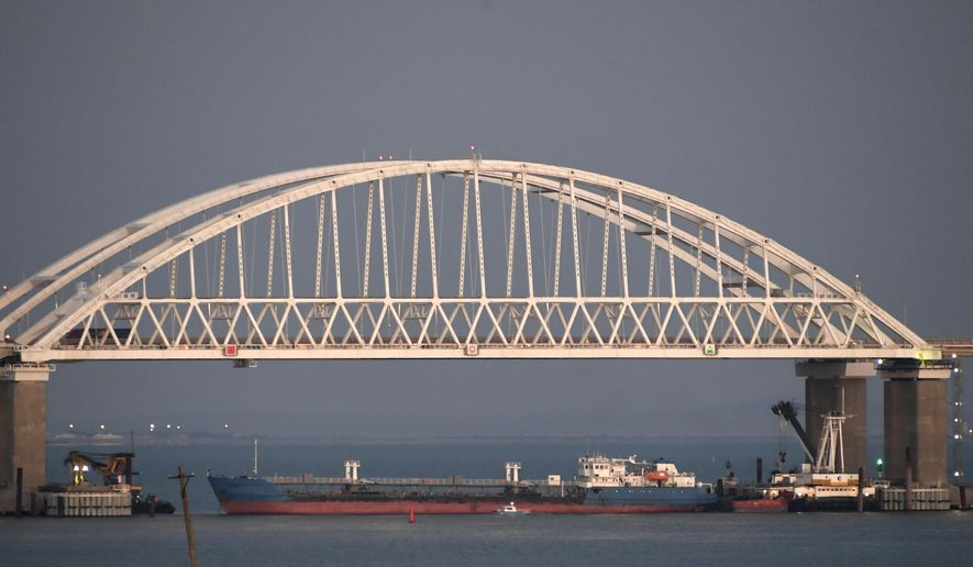 A ship under the the Kerch bridge blocks the passage to the Kerch Strait near Kerch, Crimea, Sunday, Nov. 25, 2018. Russia and Ukraine traded accusations over an incident at sea Sunday near the disputed Crimean Peninsula, increasing tensions between both countries and prompting Moscow to block passage through the Kerch Strait. (AP Photo)