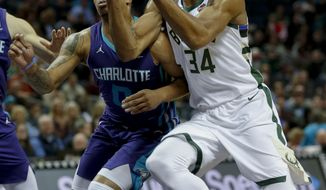 Milwaukee Bucks forward Giannis Antetokounmpo, right, of Greece, drives to the basket against Charlotte Hornets forward Miles Bridges in the first half of an NBA basketball game in Charlotte, N.C., Monday, Nov. 26, 2018. (AP Photo/Nell Redmond)