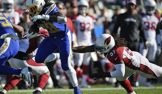 Los Angeles Chargers' Melvin Gordon (28) runs for a touchdown past Arizona Cardinals middle linebacker Josh Bynes (57) during the first half of an NFL football game Sunday, Nov. 25, 2018, in Carson, Calif. (AP Photo/Kelvin Kuo )