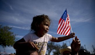 A migrant girl with a U.S. flag sits on the shoulders of a man marching with other migrants to the Chaparral border crossing in Tijuana, Mexico, Sunday, Nov. 25, 2018, as they try to reach the U.S. The mayor of Tijuana has declared a humanitarian crisis in his border city and says that he has asked the United Nations for aid to deal with the approximately 5,000 Central American migrants who have arrived in the city. (AP Photo/Ramon Espinosa)