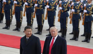 In this Nov. 9, 2017, photo U.S. President Donald Trump, right, walks with Chinese President Xi Jinping during a welcome ceremony at the Great Hall of the people in Beijing. (AP Photo/Andy Wong) **FILE**