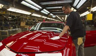 In this June 10, 2011, file photo, a worker checks the paint on a Camaro at the GM factory in Oshawa, Ontario. General Motors is closing a Canadian plant at the cost of about 2,500 jobs, but that is apparently just a piece of a much broader, company-wide restructuring that will be announced as early as Monday, Nov. 26, 2018. (Frank Gunn/The Canadian Press via AP, File)