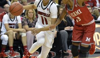 Louisville guard Arica Carter (11) attempts to drive past the defense of Miami (Ohio) guard Lauren Dickerson (13) during the second half of an NCAA college basketball game, in Louisville, Ky., Monday, Nov. 26, 2018. (AP Photo/Timothy D. Easley)