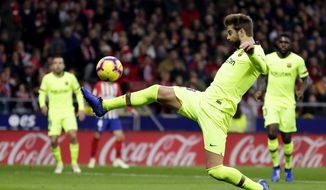 Barcelona's Gerard Pique kicks the ball during a Spanish La Liga soccer match between Atletico Madrid and FC Barcelona at the Metropolitano stadium in Madrid, Saturday, Nov. 24, 2018. (AP Photo/Manu Fernandez)