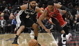 San Antonio Spurs guard Patty Mills (8) and Chicago Bulls guard Shaquille Harrison (3) go for the ball during the first half of an NBA basketball game Monday, Nov. 26, 2018, in Chicago. (AP Photo/David Banks)