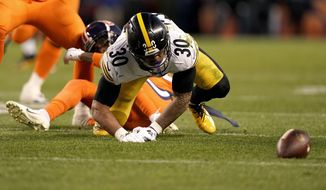 Pittsburgh Steelers running back James Conner (30) fumbles against the Denver Broncos during the second half of an NFL football game, Sunday, Nov. 25, 2018, in Denver. The Broncos recovered the ball. (AP Photo/Jack Dempsey)