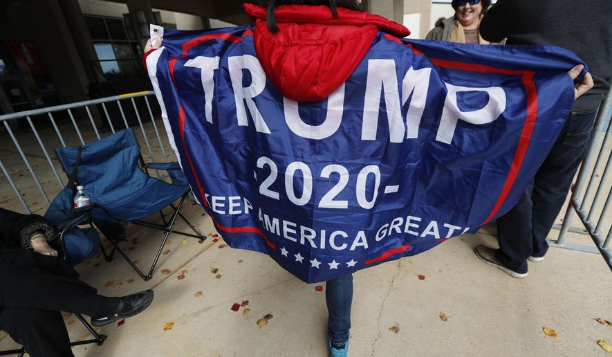 """Eva Sara Landau of Diamondhead, Miss., shows off her """"Trump 2020"""" banner cape as she waits admittance to the rally with President Donald Trump, Monday, Nov. 26, 2018, in Biloxi, Miss. Landau and others braved a cold morning to be the first in line to enter the Mississippi Coast Coliseum.(AP Photo/Rogelio V. Solis)"""