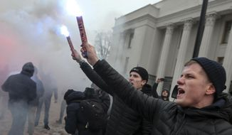 "Volunteers with the right-wing paramilitary Azov National Corps light flares during a rally on the snowy streets in front of the Ukrainian parliament in Kiev, Ukraine, Monday, Nov. 26, 2018. Some hundreds of protesters from far-right party National Corps brandished yellow-and-blue flags with the Ukrainian national trident symbol, and a banner reading 'Don't back down!"" (AP Photo/Efrem Lukatsky)"