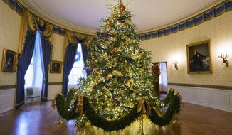 The official White House Christmas tree is seen in the Blue Room during the Christmas press preview at the White House in Washington, Monday, Nov. 26, 2018. The tree measures 18 feet tall and is dressed in over 500 feet of blue velvet ribbon embroidered in gold with each State and territory.  (AP Photo/Carolyn Kaster)