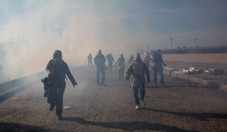 Migrants run from tear gas launched by U.S. agents, at the Mexico-U.S. border, after some got past police in Tijuana, Mexico, on Sunday. (Associated Press)