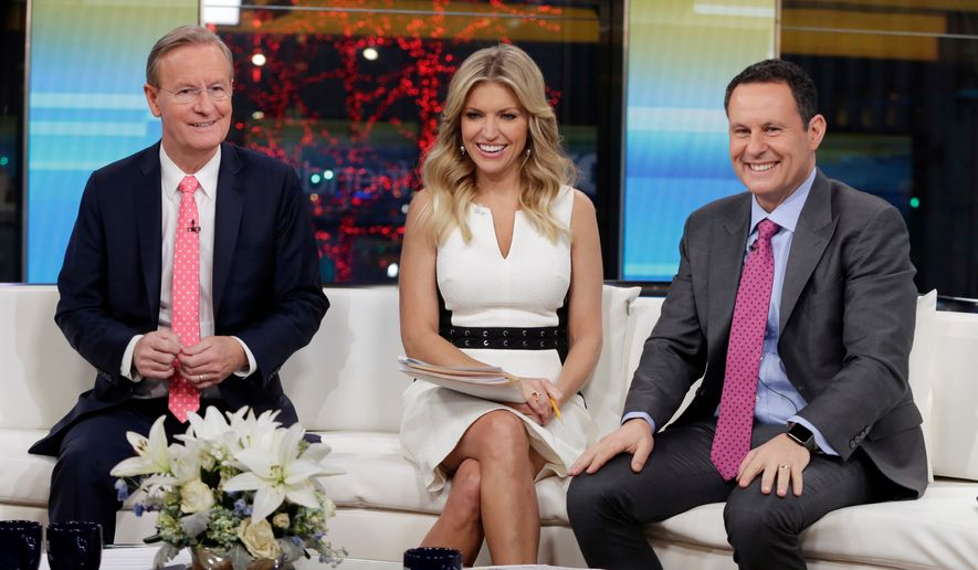 """In this Jan. 17, 2018, file photo, """"Fox & Friends"""" co-hosts, from left, Steve Doocy, Ainsley Earhardt and Brian Kilmeade appear on their set in New York. (AP Photo/Richard Drew, File)"""