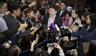 Feng Zhang, center, an institute member of Harvard and MIT's Broad Institute, is surrounded by reporters while speaking on the issue of world's first genetically edited babies after the Human Genome Editing Conference in Hong Kong, Tuesday, Nov. 27, 2018. He Jiankui, a Chinese researcher, claims that he helped make the world's first genetically edited babies twin girls whose DNA he said he altered with a powerful new tool capable of rewriting the very blueprint of life. If true, it would be a profound leap of science and ethics. (AP Photo/Vincent Yu)