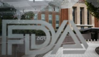 This Thursday, Aug. 2, 2018 photo shows the U.S. Food and Drug Administration building behind FDA logos at a bus stop on the agencys campus in Silver Spring, Md. An AP analysis of FDA data shows that since 2012, tens of thousands of injury and death reports have been filed in connection with devices that were cleared through a streamlined pathway that minimizes clinical trial testing. (AP Photo/Jacquelyn Martin)