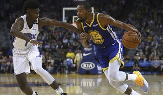 Golden State Warriors' Kevin Durant, right, drives the ball against Orlando Magic's Jonathan Isaac during the second half of an NBA basketball game Monday, Nov. 26, 2018, in Oakland, Calif. Golden State won, 116-110. (AP Photo/Ben Margot)