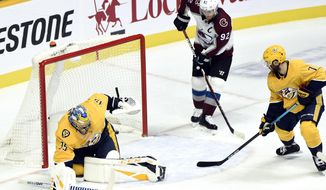 Colorado Avalanche left wing Gabriel Landeskog (92), of Sweden, watches a shot by teammate Nathan MacKinnon get past Nashville Predators goaltender Pekka Rinne (35), of Finland, for a goal during the first period of an NHL hockey game, Tuesday, Nov. 27, 2018, in Nashville, Tenn. (AP Photo/Mark Zaleski)