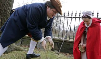 Actor-interpreters from the Boston Tea Party Ships and Museum, Tim Lawton and Jillian Couillard place commemorative markers, Tuesday, Nov. 27, 2018, at Central Burying Ground on Boston Common at the graves of participants in the Dec. 16, 1773 protest known as the Boston Tea Party. This year is the 245th anniversary of the protest during which colonists protesting taxation without representation threw British tea into Boston Harbor, considered a pivotal event that led to the American Revolution. (AP Photo/Elise Amendola)