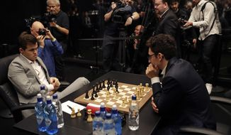 Reigning chess world champion Magnus Carlsen, left, from Norway, plays Italian-American challenger Fabiano Caruana in the first few minutes of round 12 of their World Chess Championship Match in London, Monday, Nov. 26, 2018. (AP Photo/Matt Dunham)