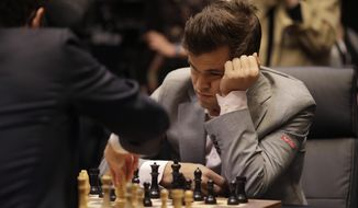 In this file photo, reigning chess world champion Magnus Carlsen, from Norway, plays Italian-American challenger Fabiano Caruana, left, in the first few minutes of round 12 of their World Chess Championship Match in London, Monday, Nov. 26, 2018. In a match played on March 21, 2019, Mr. Carlsen and his opponent Anish Giri agreed to break a longstanding rule of the game by allowing the Black pieces the first move, a symbolic statement speaking out against racism on the U.N.'s International Day for the Elimination of Racism (AP Photo/Matt Dunham). **FILE**