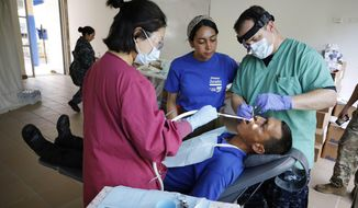 Elvis Trazadania, from Venezuela, receives free dental treatment at a public school hosting U.S. doctors from the USNS Comfort hospital ship in Riohacha, Colombia, Monday, Nov. 26, 2018. The USNS Comfort is in Colombia as part of a mission to treat local residents and Venezuelas who require urgent medical attention. (AP Photo/Fernando Vergara)