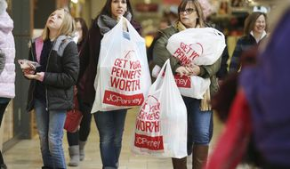 FILE- In this Nov. 23, 2018, file photo Shauna Turlipof, left, and Kathi Bankes make their way through other Black Friday shoppers at the Viewmont Mall in Scranton, Pa. On Tuesday, Nov. 27, the Conference Board releases its November index on U.S. consumer confidence. (Jake Danna Stevens/The Times-Tribune via AP, File)