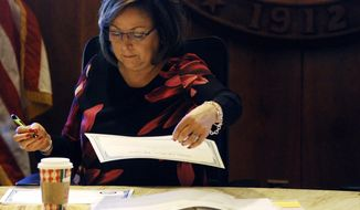 New Mexico Gov. Susana Martinez helps certify election results and order recounts in a handful of state House races in Santa Fe, N.M., on Tuesday, Nov. 27, 2018.  New Mexico is certifying election results that give Democrats unfettered control of every statewide office and the state's five-member delegation to Capitol Hill.  (AP Photo/Morgan Lee)