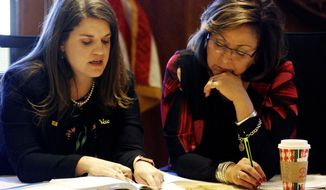 New Mexico Gov. Susana Martinez, right, and Secretary of State Maggie Toulouse Oliver, left, certify election results and order recounts in a handful of state House races in Santa Fe, N.M., on Tuesday, Nov. 27, 2018, as members of the State Canvassing Board.   New Mexico is certifying election results that give Democrats unfettered control of every statewide office and the state's five-member delegation to Capitol Hill. (AP Photo/Morgan Lee)