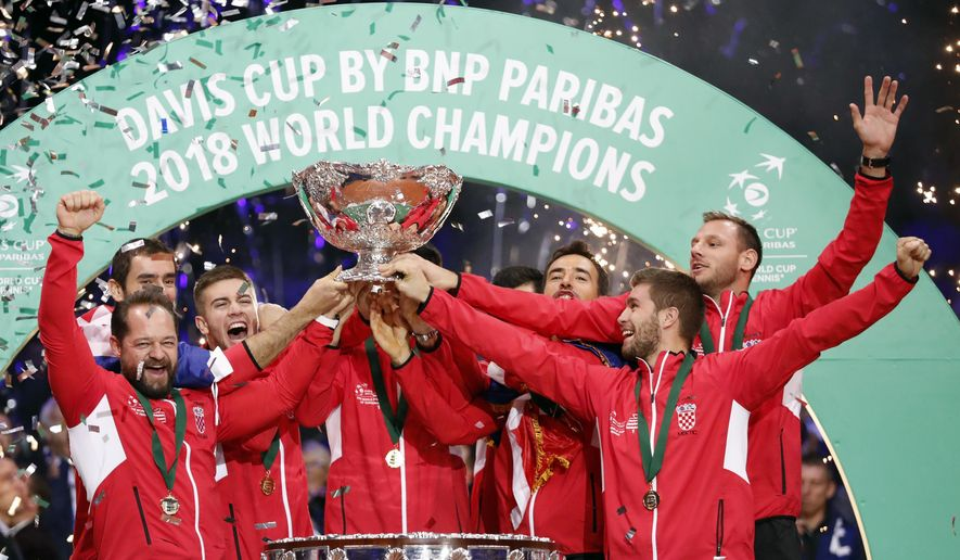 The Croatia's team captain Zeljko Krajan, left, and players lift up the cup after the team won the Davis Cup final between France and Croatia Sunday, Nov. 25, 2018 in Lille, northern France. Croatia claimed a second title in the team event following its maiden win in 2005. (AP Photo/Thibault Camus)