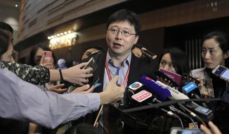 Feng Zhang, center, an institute member of Harvard and MIT's Broad Institute, reacts to reporters on the issue of world's first genetically edited babies after the Human Genome Editing Conference in Hong Kong, Tuesday, Nov. 27, 2018. He Jiankui, a Chinese researcher, claims that he helped make the world's first genetically edited babies twin girls whose DNA he said he altered with a powerful new tool capable of rewriting the very blueprint of life. If true, it would be a profound leap of science and ethics. (AP Photo/Vincent Yu)