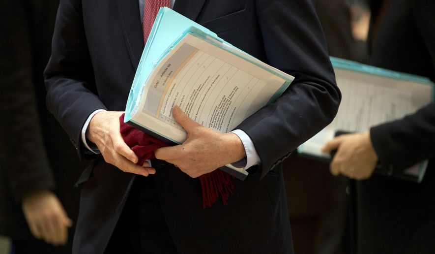 In this Tuesday, March 20, 2018 file photo, officials carry papers relating to Article 50 as they arrive for a meeting of at the Europa building in Brussels. The European Union's highest court is hearing arguments Tuesday, Nov. 27, 2018 on whether Britain could unilaterally revoke its decision to leave the EU ahead of its planned exit date of March 29, 2019. (AP Photo/Virginia Mayo, File)