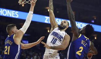 Orlando Magic's Evan Fournier, center, lays up a shot between Golden State Warriors' Jonas Jerebko (21) and Jordan Bell, right, during the first half of an NBA basketball game Monday, Nov. 26, 2018, in Oakland, Calif. (AP Photo/Ben Margot)
