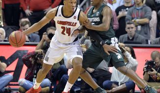 Louisville forward Dwayne Sutton (24) attempts to work his way around the defense of Michigan State guard Cassius Winston (5) during the first half of an NCAA college basketball game, in Louisville, Ky., Tuesday, Nov. 27, 2018. (AP Photo/Timothy D. Easley)
